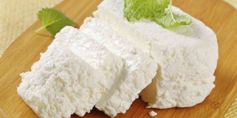 sliced ricotta cheese with a fresh mint on a wooden cutting board