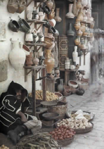 A pottery merchant takes a nap while waiting for customers.