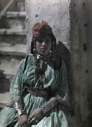 A Tunisian girl adorned in jewelry sits against a wall.
