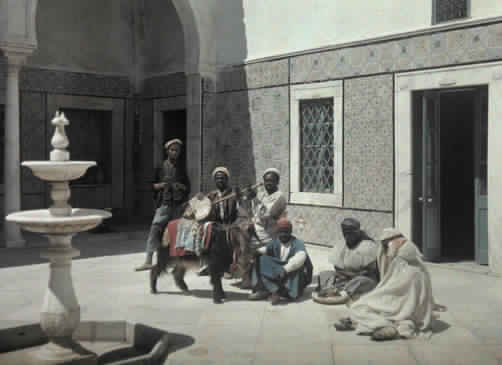 A group of men gather in a courtyard and tell of the family's fortune.