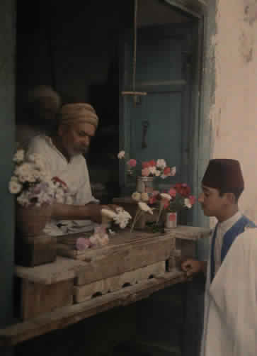 A flower merchant stands behind his shop counter and makes a sale.
